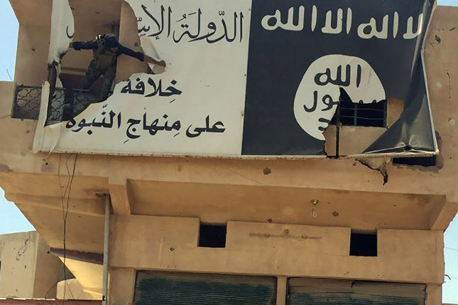 An Iraqi soldier is seen here tearing apart Islamic State propaganda on a building in the city of Fallujah in June. The Islamic State captured large swaths of territory in Syria and Iraq in 2014. Muslims worldwide have been influenced to take up the Islamic State's goal of inflicting violence on those who do not believe in its strict interpretation of Islamic law. On Monday, a 24-year-old Iraqi refugee living in Houston pleaded guilty to providing support to the Islamic State. File Photo by Abbas Mohammed/UPI