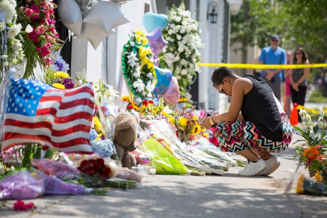 Erica Creel prays outside Emanuel African Methodist Episcopal Church on June 19, 2015, following shootings which left nine people dead on in Charleston. On Thursday a federal judge allowed a wrongful death case, accusing the FBI of incorrectly processing a background check of convicted murderer Dylann Roof to proceed. Photo by Kevin Liles/UPI