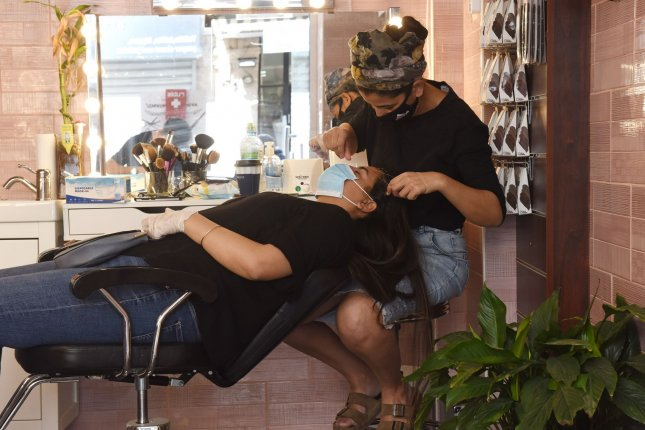 A beauty shop worker wears a face mask while threading a woman's eyebrows at a business in Jerusalem, Israel, on Friday. Photo by Debbie Hill/UPI
