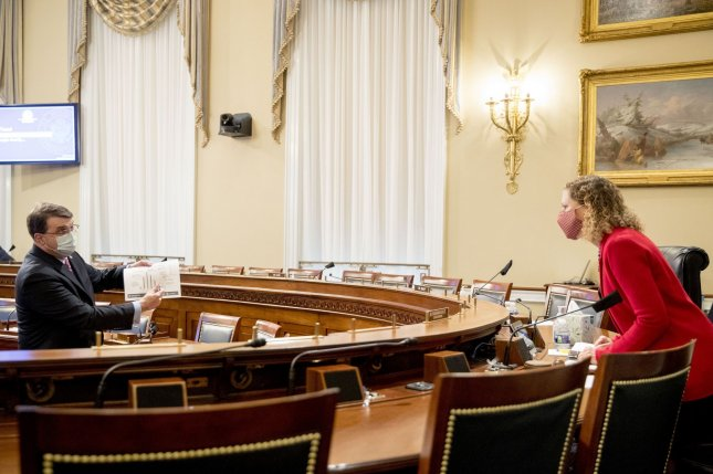 Veterans Affairs Secretary Robert Wilkie (L) holds up a document while speaking with Rep. Debbie Wasserman Schultz, D-Fla., (R) during a House subcommittee hearing Thursday in Washington. Pool Photo by Andrew Harnik/UPI