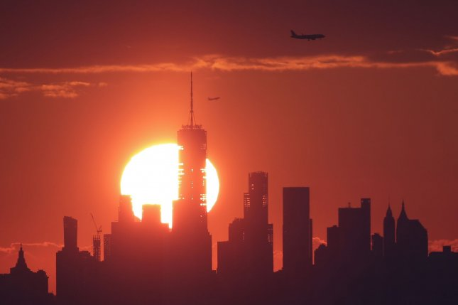 The sun rises behind One World Trade Center and the Manhattan skyline in West Orange, N.J., on Sunday. A snowstorm is pushing through the Northeast. Forecasters Photo by John Angelillo/UPI