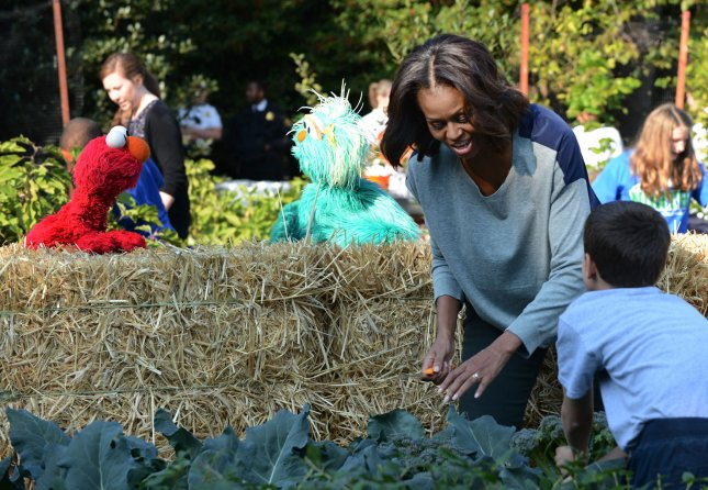 U.S. obesity in adults stable, but down in children ages 2 to 5. With Sesame Street's Elmo and Rosita looking on, First Lady Michelle Obama digs up broccoli as she helps school children in the annual fall harvest of the White House Kitchen Garden on the South Lawn of the White House in Washington, DC on October 30, 2013. Sesame Street's Elmo and Rosita joined the festivities in a marketing campaign to help children eat healthier foods. UPI/Pat Benic