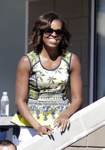 U.S. First lady Michelle Obama signs autographs from a box in Arthur Ashe Stadium at Arthur Ashe Kids Day at the USTA Billie Jean King National Tennis Center in New York, Aug. 24, 2013. UPI/John Angelillo
