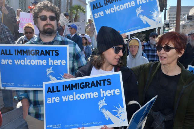Activists rally at City Hall in Los Angeles Monday to oppose President Donald Trump's efforts to build a wall along the U.S.-Mexico border. Photo by Jim Ruymen/UPI
