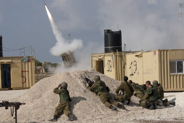 Israeli soldiers take cover as they fire an Iron Dome intercept rocket in southern Israel as Hamas fires rockets into Israel from the Gaza Strip on November 19, 2012. International peace efforts continue to stop the fighting. UPI/Mati Milstein