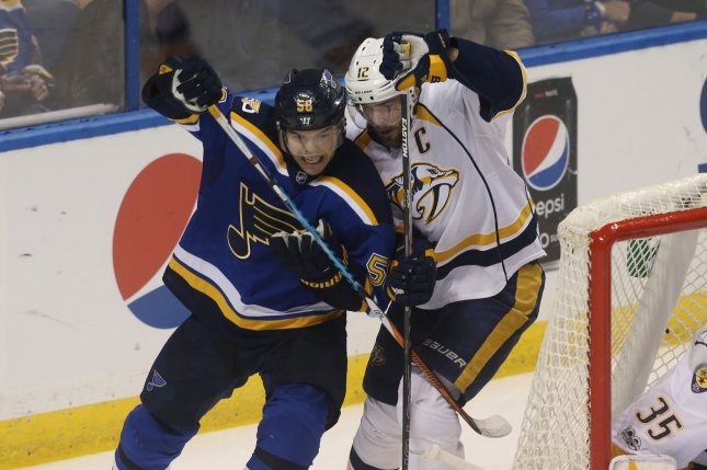 Mike Fisher of the Nashville Predators ties up the St. Louis Blues' Magnus Paajarvi during a match in April. Photo by Bill Greenblatt/UPI