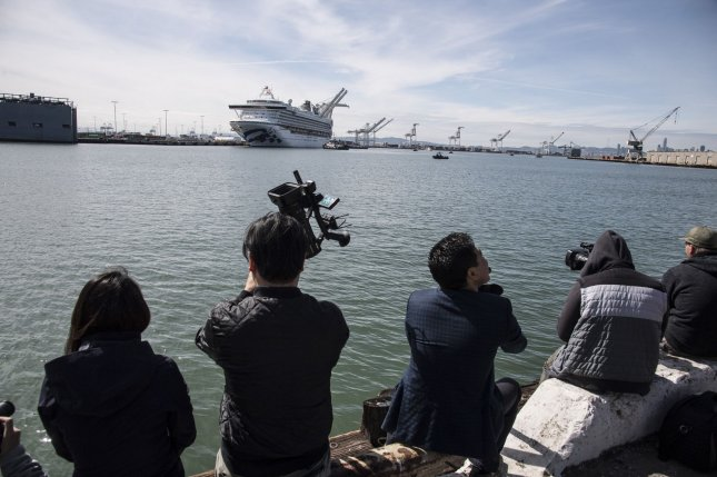 News media watch as the cruise ship Grand Princess eases into a berth in the Port of Oakland, Calif., on March 9. It was held in quarantine with 21 coronavirus cases aboard. Photo by Terry Schmitt/UPI
