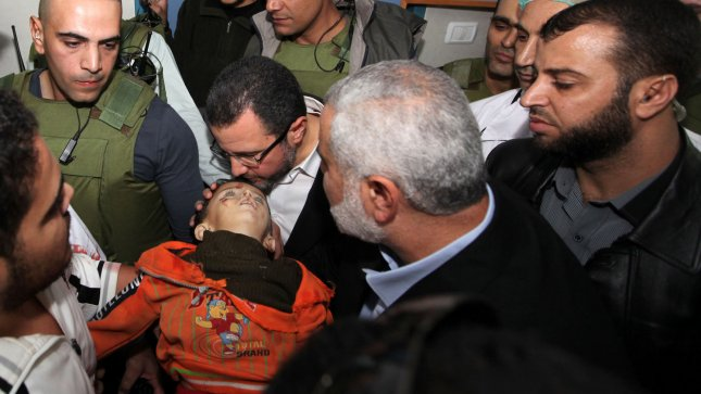 A medic carries the body of a Palestinian boy, who he claimed was killed in an Israeli strike on Gaza City, to an event in which media were invited to cover the visit of Hamas Prime Minister Ismail Haniyeh and Egyptian Prime Minister Hisham Qandil at Shifa hospital in Gaza City, November 16, 2012. UPI/Mohamed Al Ostaz/Media Palestinian Prime Minister/Handout