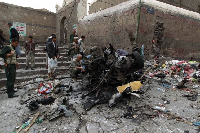 Houthi fighters inspect the wreckage of a car at the site of an attack near of Qubbat al-Mahdi Mosque in Sanaa, Yemen, on June 20. The rebels have been firing Scud missiles of North Korean origin into Saudi Arabia. File Photo by Mohammad Abdullah/UPI