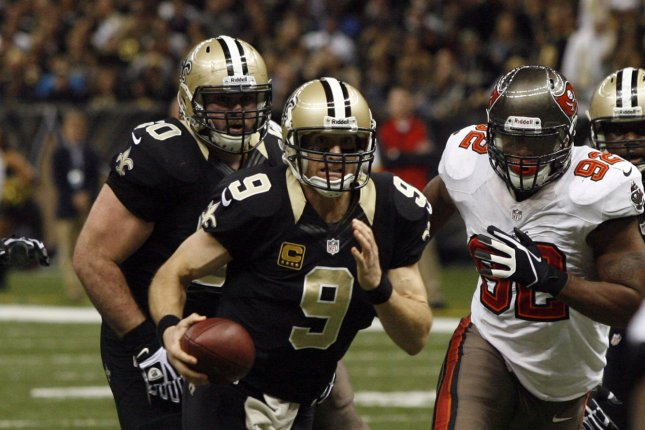 New Orleans Saints quarterback Drew Brees (9) keeps the ball and runs for a 9 yard touchdown against the Tampa Bay Buccaneers during the fourth quarter at the Mercedes-Benz Superdome in New Orleans, Louisiana on December 29, 2013. Defending on the play is Buccaneers defensive end William Gholston (92). UPI/A.J. Sisco