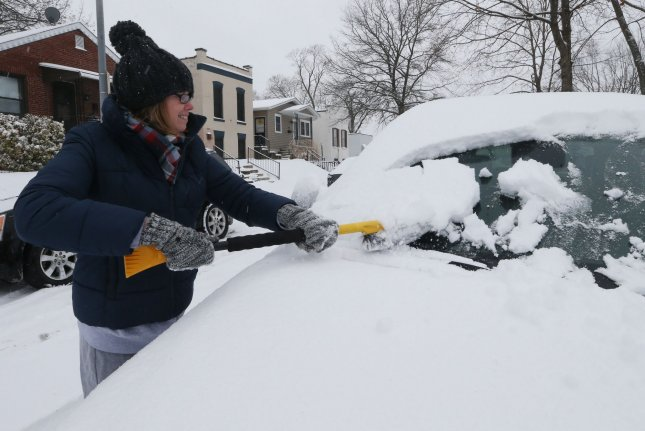 Motorist Julie French uses a snow brush to clear her windows during a snow storm in St. Louis on December 16, 2019. File Photo by Bill Greenblatt/UPI