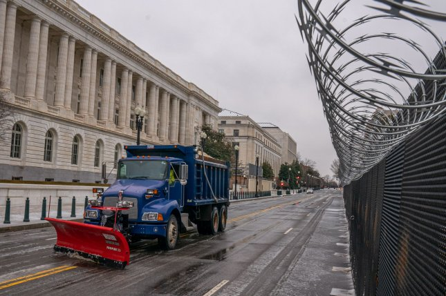 A truck snow plows the streets around the U.S. Capitol as a winter storm passes through the Northeast corridor in Washington, D.C. Thursday, Photo by Ken Cedeno/UPI