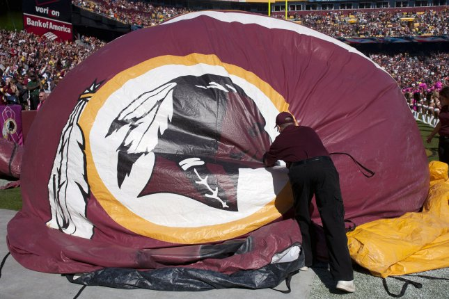 A member of the Washington Redskins maintenance staff takes down an inflatable helmet with the Washington Redskins logo on it. UPI/Kevin Dietsch