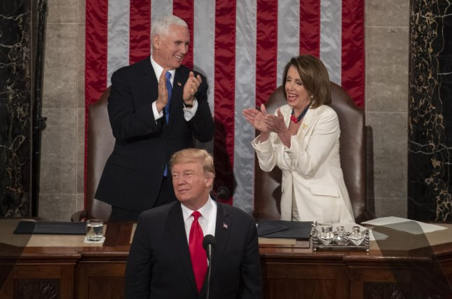 Vice President Mike Pence and Speaker of the House Nancy Pelose smile and applaud as President Donald Trump makes a comment in support of women during his State of the Union address on Tuesday. Photo by Pat Benic/UPI