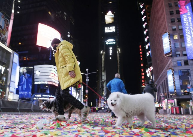 A man walks two dogs over the confetti that remains on the ground after the New Year's Eve and New Years Day celebration which was closed to the public due to the pandemic. Photo by John Angelillo/UPI