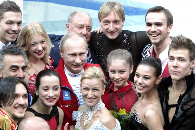 Russian President Vladimir Putin poses with members of Russia's gold medal-winning figure-skating team at the Sochi Olympic Games in 2014. Russia has been banned from next year's Olympics, leaving its athletes out in the cold. File Photo by Maya Vidon-White/UPI