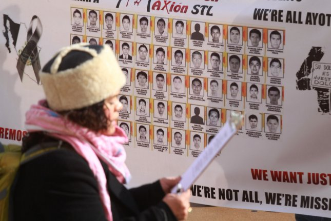 A woman, only known as Jessie, a member of the Latinos en Accion, a group that advocates for rights of Latinos in the United States, reads a poem dedicated to the 43 students that disappeared in Mexico in September 2014, during a protest in St. Louis in Devember 2014. An independent investigation faulted state and federal Mexican police. UPI/BIll Greenblatt