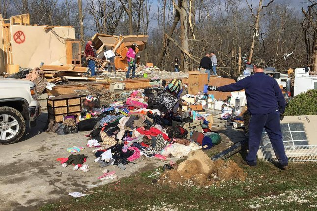 People clear debris from their damaged home in Perryville, Mo., on Wednesday following a tornado that killed one person, injured 20 and damaged nearly 100 homes. The person who died was in a vehicle that was blown off a highway by strong winds. Photo by Bob Hoehn/UPI