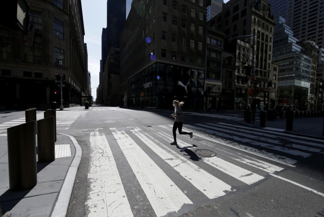 A woman jogs on an empty Fifth Avenue in New York City on Sunday. New York City Mayor Bill de Blasio said in an update Monday he is seeing signs of progress against the coronavirus disease. Photo by John Angelillo/UPI