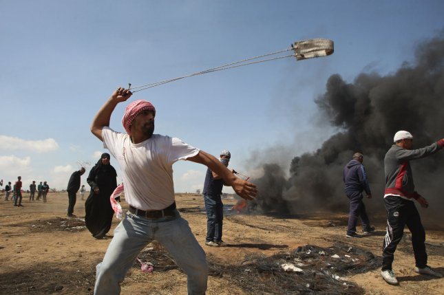 A Palestinian youth used a slingshot to hurl stones during clashes with Israeli forces along the border with the Gaza Strip, east of Khan Younis on Friday, as Palestinians demonstrated for the right to return to their historic homelands in what is now Israel. Fifty-two Palestinians have been killed by Israeli fire since protests and clashes began on March 30. Photo by Ismael Mohamad/UPI