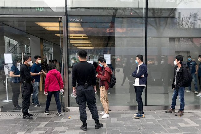 Customers stand in line outside Apple's flagship store in Beijing, China, before it opens on April 2. A few locations in the United States will reopen this week. File Photo by Stephen Shaver/UPI