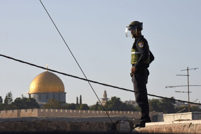 An Israeli border police officer on Wednesday stands on a wall overlooking the Temple Mount, or Noble Sancutary, near a site where Israel is installing concrete blocks at the entrance to the Palestinian neighborhood of Ras al-Amud in East Jerusalem. Israel is setting up roadblocks at the entrances to several Arab neighborhoods around Jerusalem and deploying hundreds of troops in major cities following a series of shooting and stabbing attacks by Palestinians on Israelis. Photo by Debbie Hill/ UPI