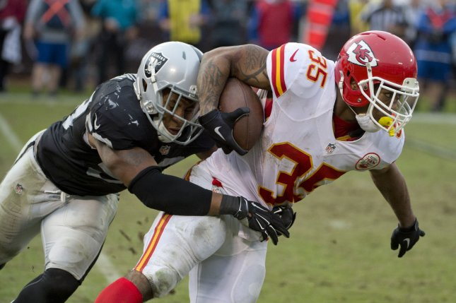 Former Oakland Raiders linebacker Malcolm Smith (L) drags down Kansas City Chiefs RB Charcandrick West (35) after a two-yard gain in the third quarter at O.co Coliseum in Oakland, California on December 6, 2015. File photo by Terry Schmitt/UPI