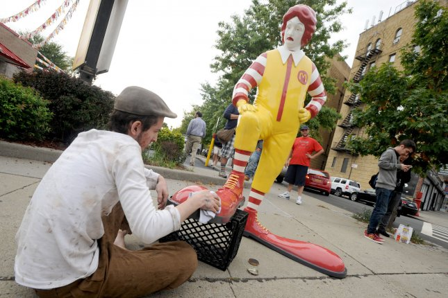 A fiberglass replica of Ronald McDonald having his shoes shined by a real live boy will visit the sidewalk outside a different McDonalds every lunchtime for the next week as a work of British street artist Banksy in New York City on October 16, 2013. UPI/Dennis Van Tine