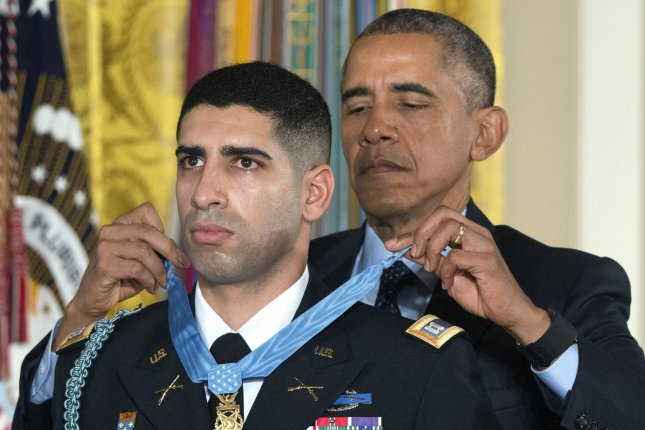 President Barack Obama awards the Medal of Honor to Captain Florent A. Groberg, U.S. Army (Ret), during a ceremony at the White House in Washington, D.C. on November 12, 2015. Capt. Groberg is being recognized for courageous actions while serving during combat operations in Asadabad, Kunar Province, Afghanistan on August 8, 2012. Groberg tackled a suicide bomber, saving fellow service members while receiving serious wounds. Photo by Kevin Dietsch/UPI