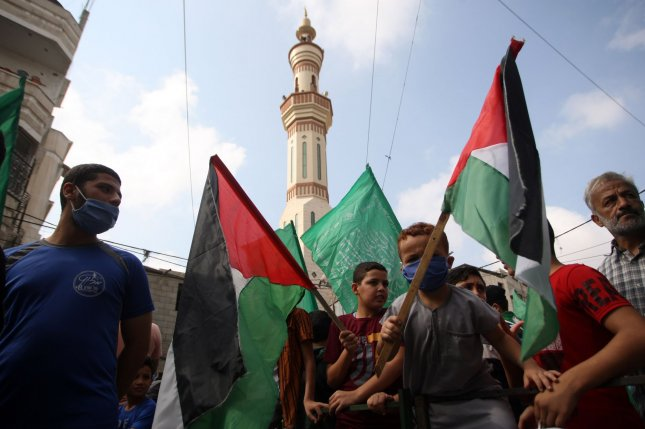 Palestinians carry flags as they protest against the publications of a cartoon of Prophet Mohammad in France during a demonstration in Rafah in the southern Gaza Strip Friday. Photo by Ismael Mohamad/UPI