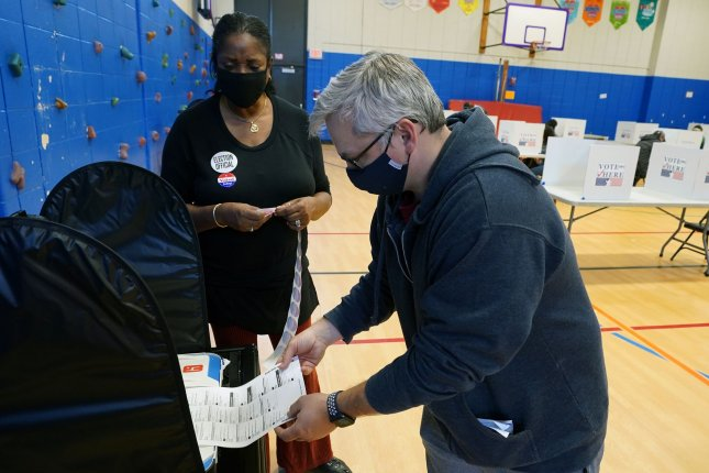 A voter places his vote into a collecting machine at the Craig School in Creve Coeur, Mo., on Tuesday. Gubernatorial candidate and incumbent Mike Parson retained his seat on Tuesday night. Photo by Bill Greenblatt/UPI