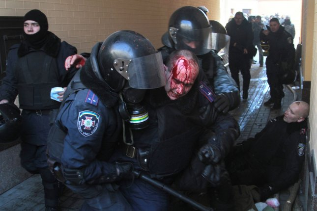 Ukrainian riot police help an injured officer during a clash with anti-government protesters outside the Parliament building in Kiev on February 18, 2014. File Photo by Sergey Starostenko/UPI