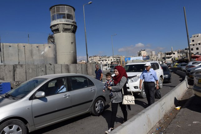 Palestinians walk by cars waiting in line to cross the Israeli controlled Qalandiya Checkpoint, between Ramallah, West Bank and Jerusalem, on Tuesday. The Israeli Defense Ministry has announced that all crossings to Israel for Palestinians from the West Bank and Gaza will be closed for 11 days during the Jewish feast of Sukkot. The closure will impact tens of thousands of Palestinians who legally work in Israel. The crossings will be closed to Palestinians from Wednesday through October 14 except for humanitarian or medical cases. Photo by Debbie Hill/UPI