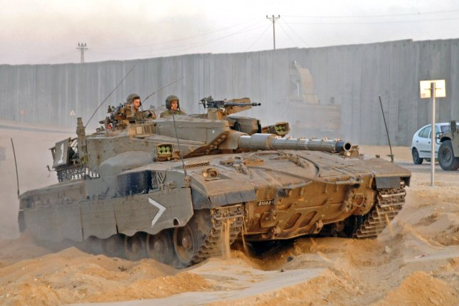 An Israel Defense Force tank drives along the security wall just north of the Gaza Strip. Defense Minister Natfali Bennett signed an order on Sunday calling for an five-year overhaul of IDF capabilities in light of expected threats. File Photo by Joerg Waizmann/UPI