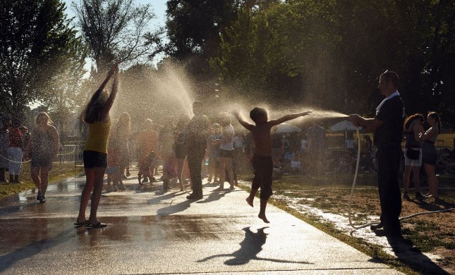 Children are sprayed down with water at a cooling station while waiting for fire works on the National Mall near the Washington Monument in Washington on July 4, 2010. Temperatures reached the mid nineties in the Nation's Capital. UPI/Roger L. Wollenberg
