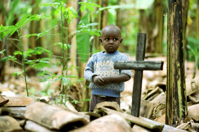 A young boy stands next to the grave of a parent who died of HIV/AIDS in Uganda. File Photo courtesy Bill Youngblood/World Vision Photo/UPI