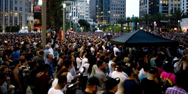 People jam the lawn of the Dr. Phillips Center for the performing arts to hold a candlelight vigil after the shooting at the Pluse nightclub in Orlando, Fla. File Photo by Gary I Rothstein/UPI