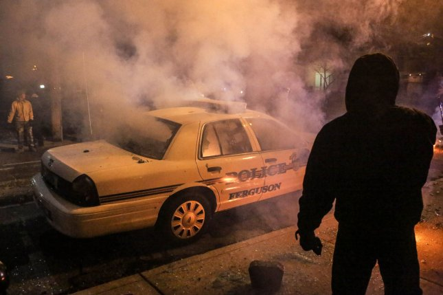 Demonstrators attack a police car during a second night of protests on the streets of Ferguson, Missouri late on November 25, 2014. A grand jury decided not to indict police officer Darren Wilson in the killing of Michael Brown on November 24, 2014. Wilson killed Brown in an August 9, 2014 incident that has sparked racial tension and riots. UPI/Lawrence Bryant