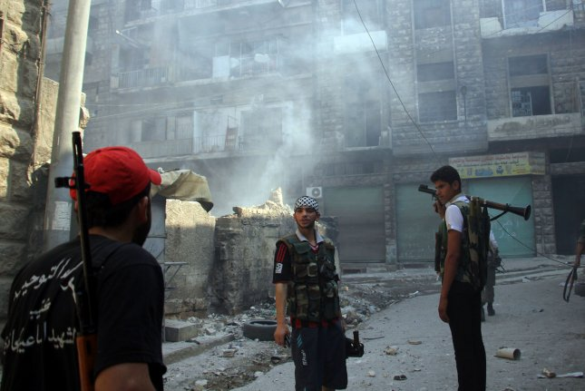 Syrian rebels, including Jabhat Fateh al-Sham -- formerly the al-Nusra Front, a former al-Qaida affiliate, on Friday launched an offensive in Aleppo to break President Bashar al-Assad's siege of the embattled eastern section of the city. In this image, Syrian rebels are seen after a government bombing in Aleppo in 2012. File Photo by Ahmad Deeb/UPI