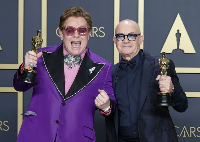 Elton John (L) and Bernie Taupin, winners of Best Original Song for (I'm Gonna) Love Me Again for Rocketman, arrive backstage with their Oscars, during the 92nd annual Academy Awards in Los Angeles in 2020. The biopic is one of 2,500 movies Paramount+ is adding to its streaming library this summer. File Photo by John Angelillo/UPI
