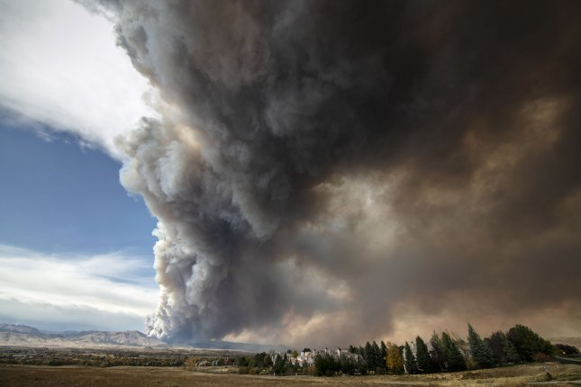 A massive plume of smoke rises from the CalWood wildfire in the Boulder County foothills as seen from Niwot, Colo., on October 17. Photo by Bob Strong/UPI