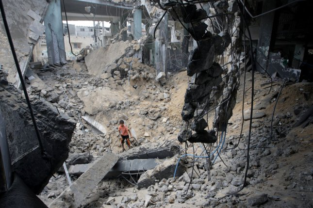 Palestinians inspect the rubble of the al-Faroq mosque after an overnight Israeli military strike in Rafah, Gaza Strip on July 22, 2014. UN chief Ban Ki-moon and U.S. Secretary of State John Kerry are in the Middle East in a bid to broker a truce between Israel and Hamas after two weeks of fighting that has left hundreds dead. UPI/Ismael Mohamad