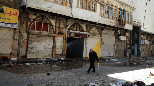 A Syrian man walks near damaged buildings in downtown Homs, Syria, March 21, 2012. UPI