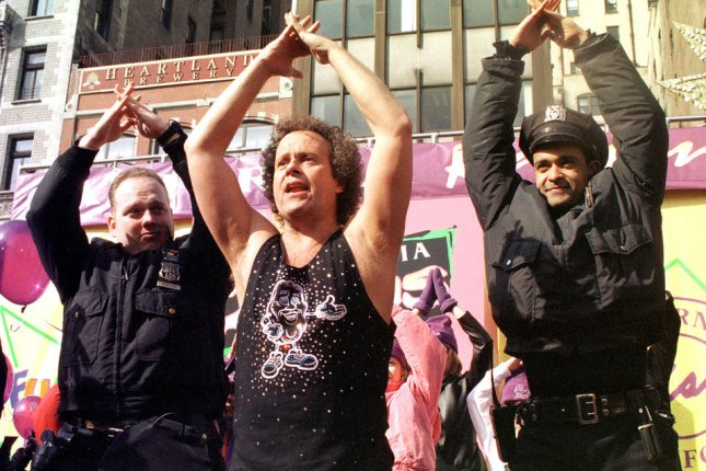Richard Simmons convinces New York Police officers to join an impromptu exercise session on February 10, 2000 during a press conference in New York. Simmons has sued the National Enquirer over false stories published about how he is undergoing a sex-change. File Photo by Ezio Petersen/UPI