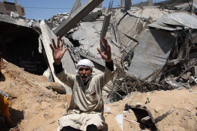 A Palestinian man cries over his destroyed house after overnight Israeli airstrikes in town of Rafah, southern Gaza Strip, on Sunday. Photo by Ismael Mohamad/UPI.