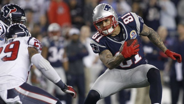 New England Patriots tight end Aaron Hernandez attempts to dodge a tackle by Houston Texans cornerback Kareem Jackson. Hernandez's fiancee has been linked to Hernandez's murder case for potentially hiding evidence. UPI/Matthew Healey