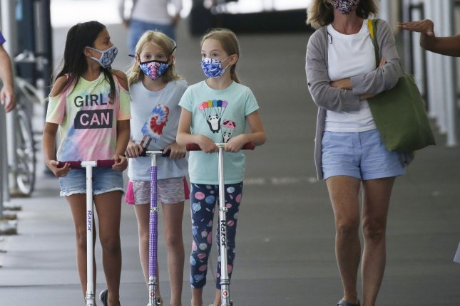 Three children on scooters wear face masks to protect from and prevent the spread of coronavirus as they move together on the sidewalk in New York City in August. Photo by John Angelillo/UPI