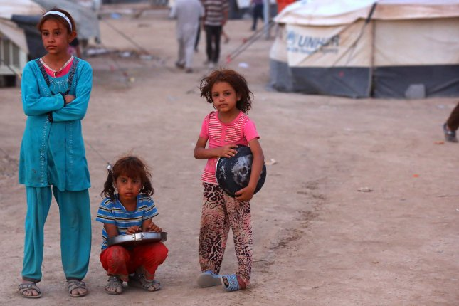Iraqi refugees girls, who fled from the violence in Mosul, wait up to receive free food during the holy fasting month of Ramadan inside the Khazer refugee camp on the outskirts of Arbil, in Iraq's Kurdistan region.Tens of thousands of people have fled Iraq's second largest city of Mosul after it was overrun by ISIS (Islamic State of Iraq and Syria) militants. Many have been temporarily housed at various IDP camps. UPI/Ceerwan Aziz