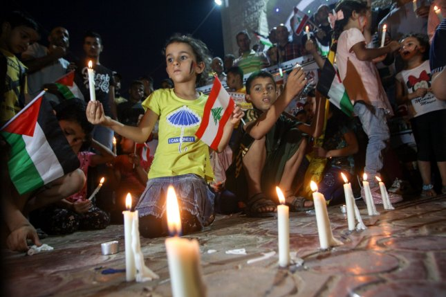 Palestinian children in Rafah in southern Gaza light candles and carry the flags of Lebanon to show support for the Lebanese people on Wednesday. Photo by Ismael Mohamad/UPI