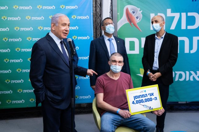 Israeli Prime Minister Benjamin Netanyahu poses with Israel's 4 millionth vaccine recipient at the Leumit Health Care Services vaccination facility in Jerusalem, Israel, on Tuesday. Photo by Alex Kolomoisky/UPI/Pool